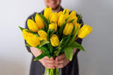 Fototapeta Tulips - man holds bouquet of yellow tulips in front of him. romantic gift for woman. white background