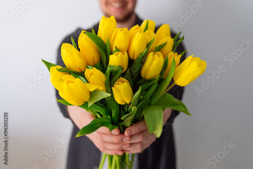 Fototapeta premium man holds bouquet of yellow tulips in front of him. romantic gift for woman. white background