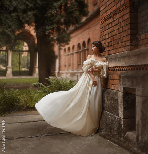 A young lady stands at the wall of an ancient castle looking with hope in the distance. Emotion waiting for the long-awaited. A white vintage dress flutters in the wind. Artistic Photography