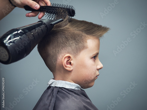 Fotografie, Obraz  Side view of cute boy getting hairstyle by hairdresser in barbershop