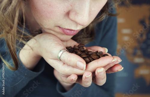 Staande foto Koffiebonen Granos de café tostado de importación en la mano de una mujer