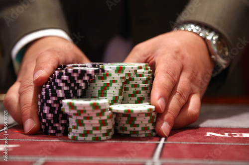 Fotografie, Obraz  Player at gambling table pusing large stack of chips