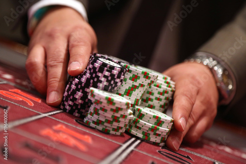 Photo Player at gambling table pusing large stack of chips