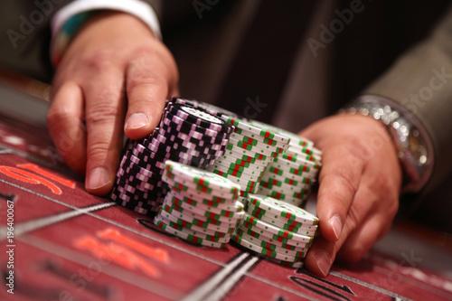 Player at gambling table pusing large stack of chips Wallpaper Mural