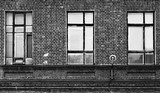 Fragment fasady starego budynku z cegły. Wysokie okna i materiały teksturowane. - 196407248