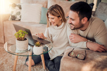 Young Couple Relaxing On Sofa With Laptop