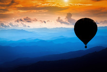 Silhouette Colorful Hot Air Balloons Flying Over Mountains Landscape With Dramatic Sunset Sky And Clouds