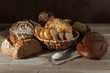 Set of wheat and rye bread with a spoon of salt on a wooden background
