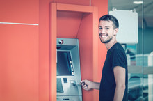Young Smiling Man Using ATM Ma...