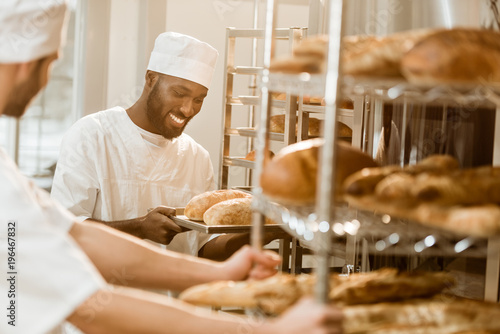 Photo handsome bakers working together at baking manufacture