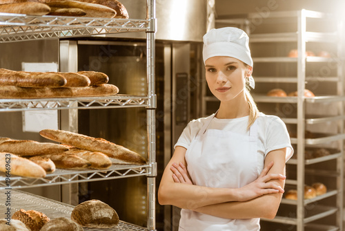 Fotografia, Obraz young female baker with crossed arms near shelves with freshly baked bread on ba