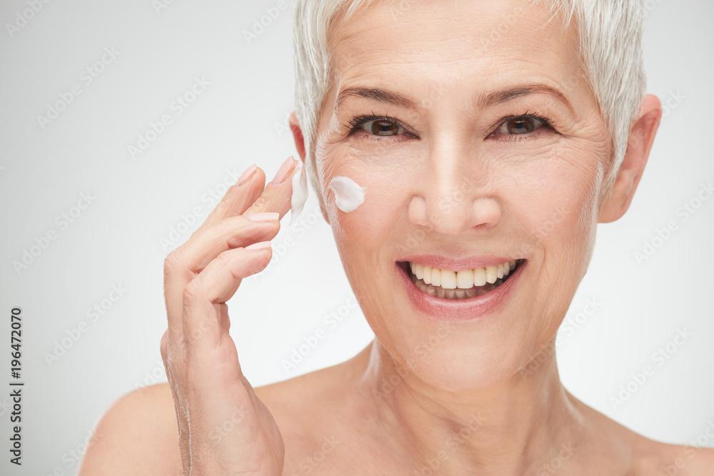 Fototapety, obrazy: Head shot of beautiful senior woman putting on the cream.