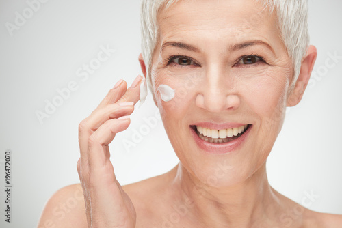 Fotografía Head shot of beautiful senior woman putting on the cream.