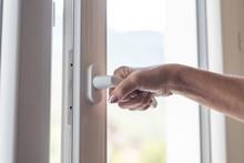 Female Hand Opening A Window