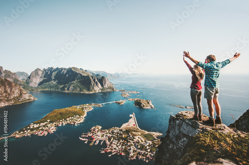 Foto auf AluDibond Blau türkis Happy Couple love and travel raised hands on cliff in Norway man and woman family travelers lifestyle concept summer vacations outdoor Lofoten islands