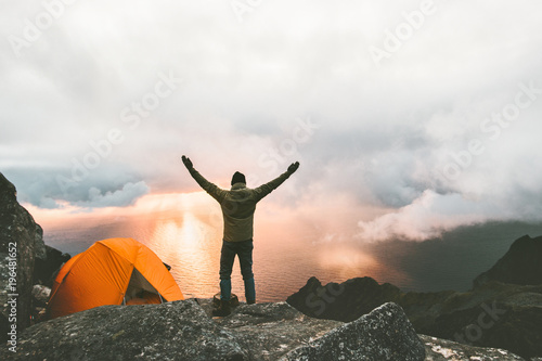 Poster Camping Man traveler happy raised hands on mountain top near of tent camping outdoor Travel adventure lifestyle success concept hiking active vacations enjoying sunset view
