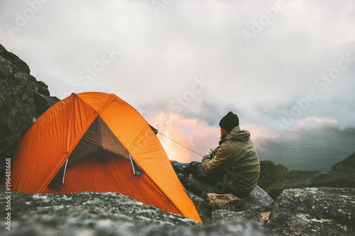 Poster Camping Man traveler relaxing in mountains near of tent camping gear outdoor Travel adventure lifestyle concept hiking active vacations