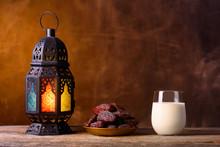 Holy Month Of Ramadan Concept. Righteous Muslim Lifestyle. Fasting. Ramadan Lantern, Dates, Glass Of Milk. Dark Brown Background.