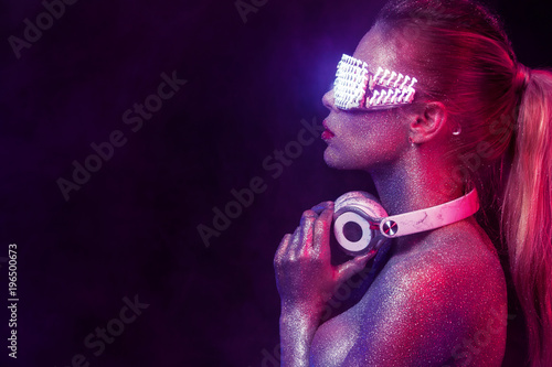 Magasin de musique Beautyful girl with glitter and sparkles on her face and body. Portrait of sexy TDJ with headphones and neon sunglasses