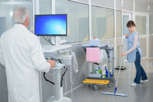 Woman Cleaning Hospital Corridor, Doctor Using Computer