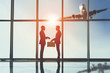 Silhouette view of two young businessmen are standing with suitcase in modern office with panoramic windows