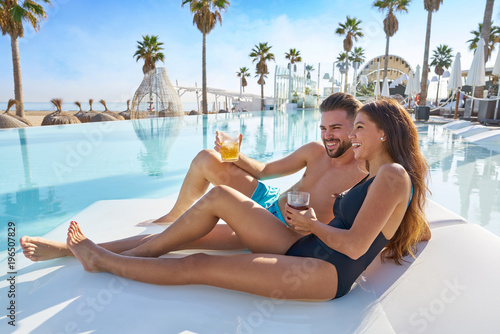 Fototapeta Young couple on pool hammock at beach resort