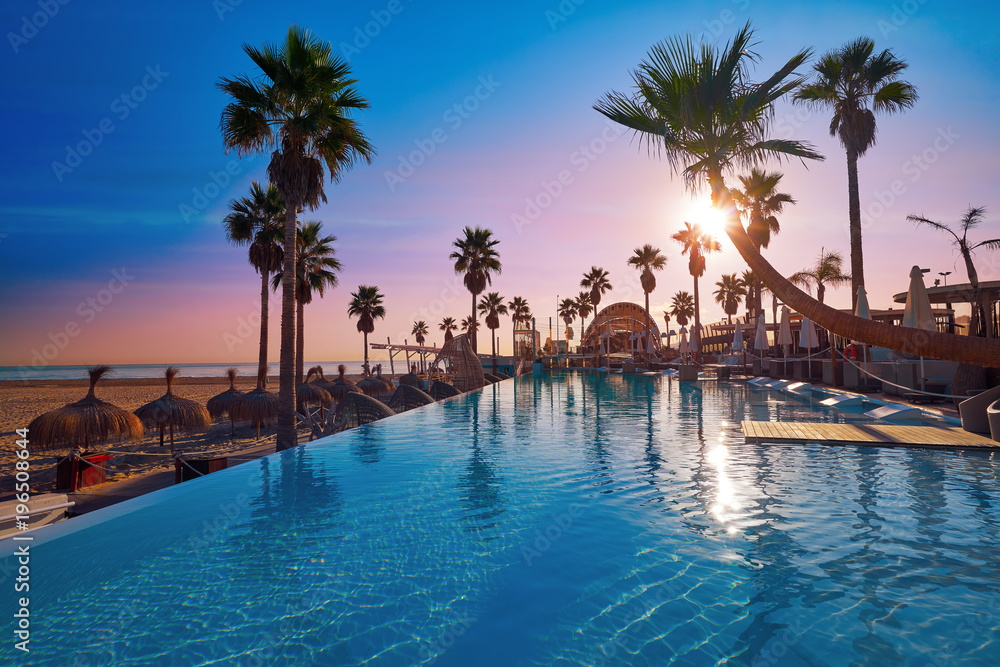 Fototapeta Resort pool in a beach with palm trees sunrise