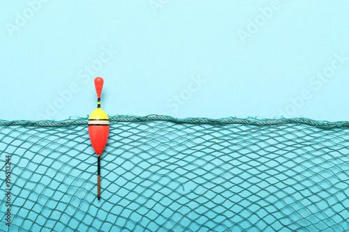 Fototapeta Fishing net with bobber on blue background