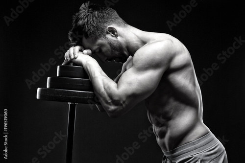 Poster Ontspanning Bodybuilder relaxng in front of black background