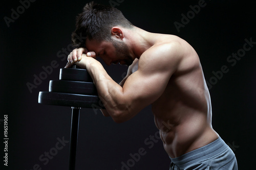 Bodybuilder relaxng in front of black background