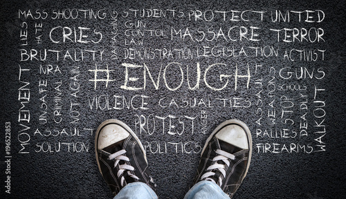 Photo Teen in jeans and canvas shoes standing on asphalt road with # ENOUGH word cloud