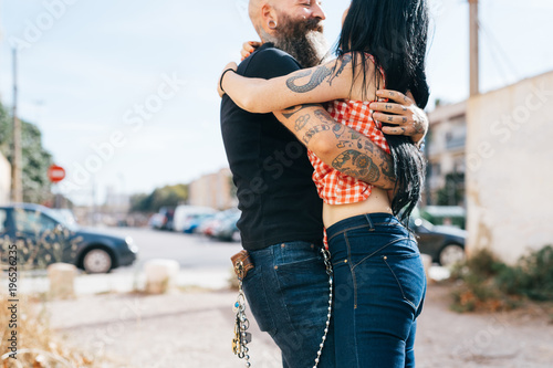 Mature hipster couple hugging each other