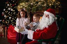 Young Girl And Boy Visiting Santa, Receiving Gifts