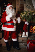 Santa Claus Standing Beside Fireplace, Holding Glass Of Milk