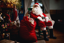 Portrait Of Santa Claus, Sitting In Chair With Sack Full Of Presents