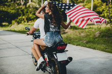 Young Couple Holding Up American Flag While Riding Motorcycle On Rural Road, Krabi, Thailand, Rear View