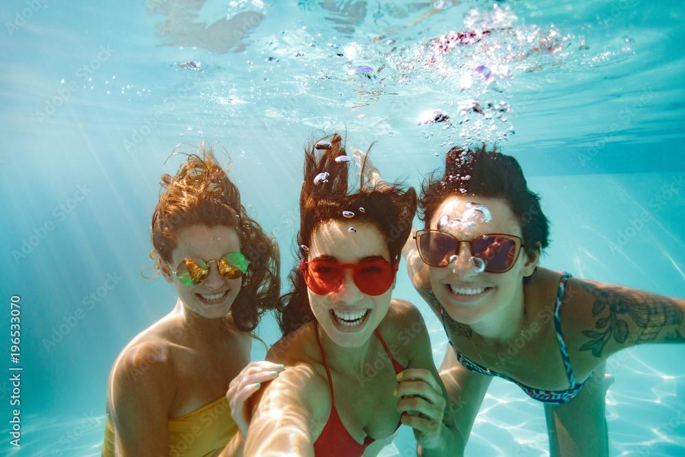 Fototapety, obrazy: Cheerful friends making selfie underwater in pool