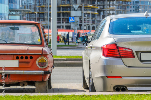 Rear view of two cars of different eras standing side by side in the city. The concept of technology development © v_sot