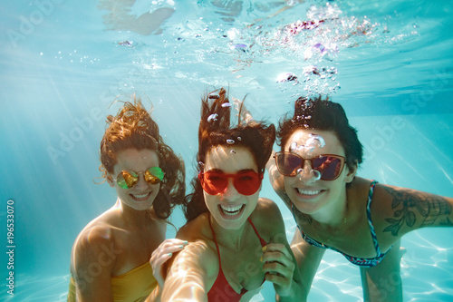 Fotomural Cheerful friends making selfie underwater in pool