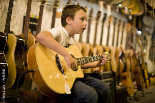 Staande foto Muziekwinkel Young boy strumming an acoustic guitar inside a music shop.
