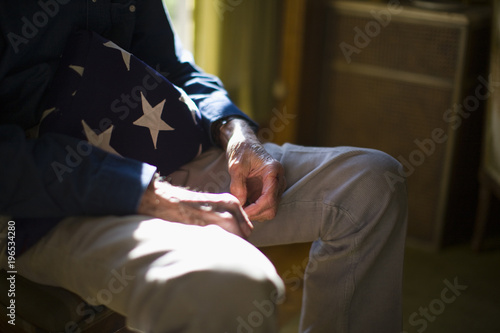 Mid section of a senior man with folded American flag sitting at home