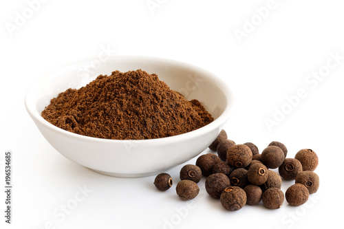 Fototapeta Ground allspice in white ceramic bowl isolated on white. Whole allspice. obraz