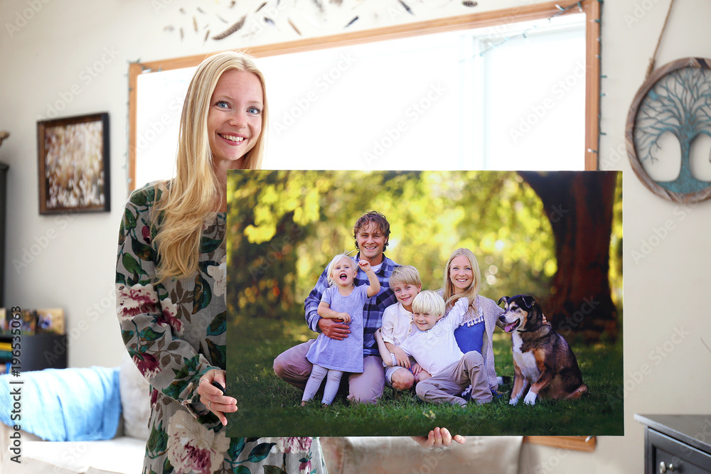 Fototapety, obrazy: Happy Young Woman Holding Canvas Print of Family Portrait
