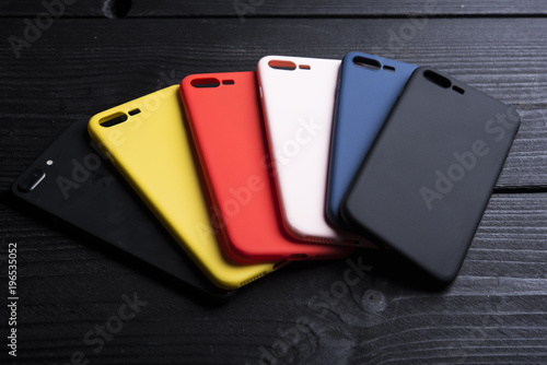 Mobile multicolored phone covers or phone cases on black wooden background Billede på lærred