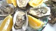 Fresh oysters closeup rotating in blue plate, served wooden table with oysters, lemon and ice. 4K Ultra high definition 3840X2160