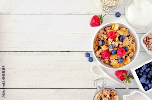 Photo Cereal and ingredients for a healthy breakfast forming a side border over a white wood background