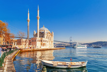 Ortakoy Cami - Famous And Popular Landmark In Istanbul, Turkey. Lovely Spring Scenery With Fishing Boat At Foreground And Old Historical Mosque Ortakoy And Istanbul Bosporus Bridge At Background.