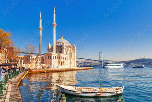 Poster Turkey Ortakoy cami - famous and popular landmark in Istanbul, Turkey. Lovely spring scenery with fishing boat at foreground and old historical mosque Ortakoy and Istanbul Bosporus bridge at background.