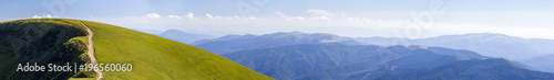 Spoed Foto op Canvas Heuvel Panorama of green hills in summer mountains with gravel road for travelling by car
