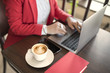 Business woman indoor with coffee and laptop on wooden table
